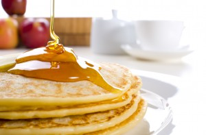 Pancakes with butter and syrup. Coffee, sugar and fruit in background.