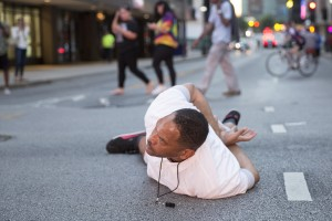 "A man lays on the ground after yelling ""Don't shoot me"" at police during a rally in Dallas, Texas, on Thursday, July 7, 2016 to protest the deaths of Alton Sterling and Philando Castile. Black motorist Philando Castile, 32, a school cafeteria worker, was shot at close range by a Minnesota cop and seen bleeding to death in a graphic video shot by his girlfriend that went viral Thursday, the second fatal police shooting to rock America in as many days. / AFP PHOTO / Laura Buckman"