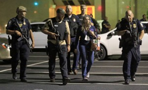 DALLAS, TX - JULY 8: Dallas police officers escort a woman near the scene where eleven Dallas police officers were shot and five have now died on July 7, 2016 in Dallas, Texas. According to reports, shots were fired during a protest being held in downtown Dallas in response to recent fatal shootings of two black men by police - Alton Sterling on July 5, 2016 in Baton Rouge, Louisiana and Philando Castile on July 6, 2016, in Falcon Heights, Minnesota. Ron Jenkins/Getty Images/AFP