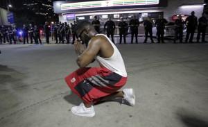 RL01 DALLAS (ESTADOS UNIDOS) 08/07/2016.- Un joven se arrodilla frente a los policías desplegados en la esquina de Ross Avenue y Griffin street durante una manifestación contra la violencia policial hacia los negros en EEUU, que se saldó con cinco agentes muertos en in tiroteo, en Dallas, Estados Unidos, hoy, 8 de julio de 2016. Los cinco policías fallecieron y otros 6 resultaron heridos cuando dos francotiradores les dispararon desde posiciones elevadas, informó la Policía de la ciudad. Uno de los sospechosos de haber protagonizado los disparos sigue atrincherado en un aparcamiento en el centro de Dallas, desde donde ha asegurado que ha colocado varias bombas en todo el edificio y en otras partes de la ciudad. Al margen del sospechoso atrincherado en el aparcamiento, la Policía mantiene en custodia a tres personas, incluyendo a una mujer que fue detenida en el aparcamiento y a otros dos individuos que circulaban por la autopista en un Mercedes. EFE/Ralph Lauer