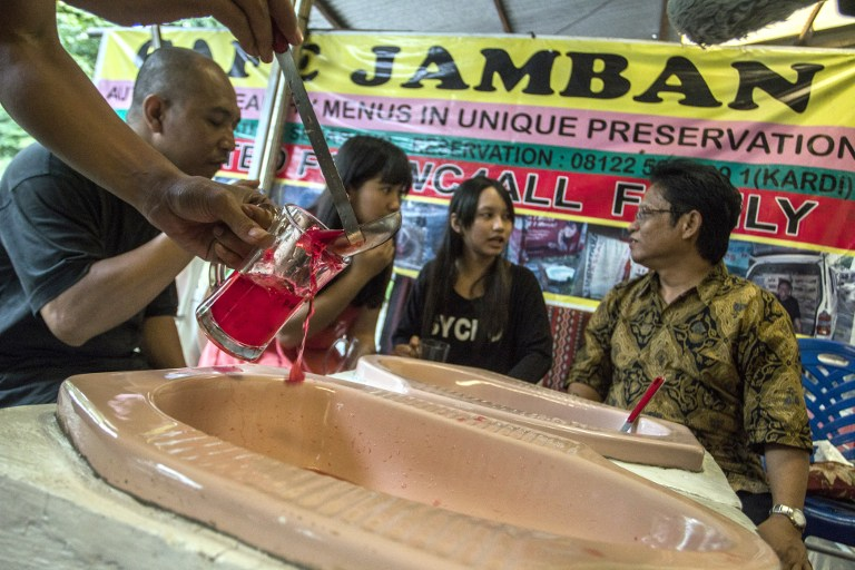 """This picture taken on July 16, 2016 shows customers having a meal at the """"Jamban Cafe"""" in the city of Semarang on Java island, a small eatery where a handful of diners sit on upright toilets around a table where food is served in two squat toilets. The toilet-themed cafe where customers dine on meatballs floating in soup-filled latrines may not be everyone's idea of haute cuisine, but Indonesians are flocking to become privy to the latest lavatorial trend. / AFP PHOTO / SURYO WIBOWO"""
