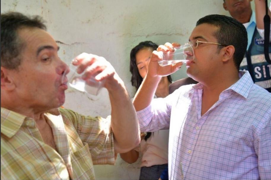 Armando Cuello, de Emdupar, y el alcalde Augusto Ramírez toman agua de la llave para mostrar que no está envenenada.