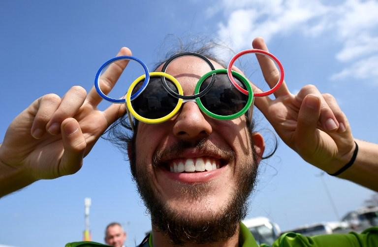 Voluntario con gafas alusivas a los Juegos Olímpicos. Pulzo.com