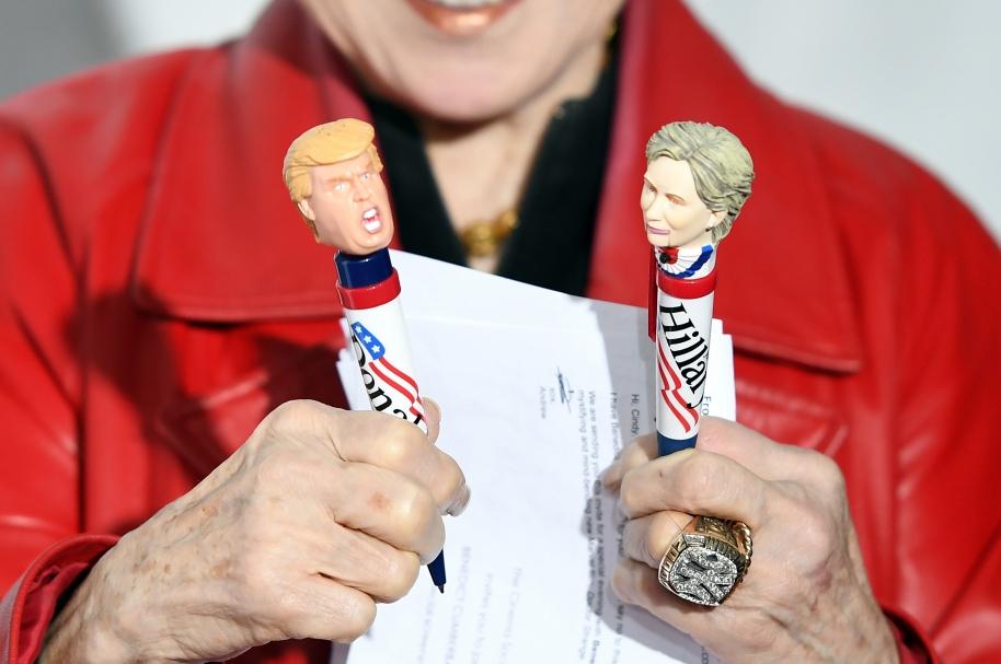 Una mujer sostiene esferos conmemorativos de Donald Trump y Hillary Clinton