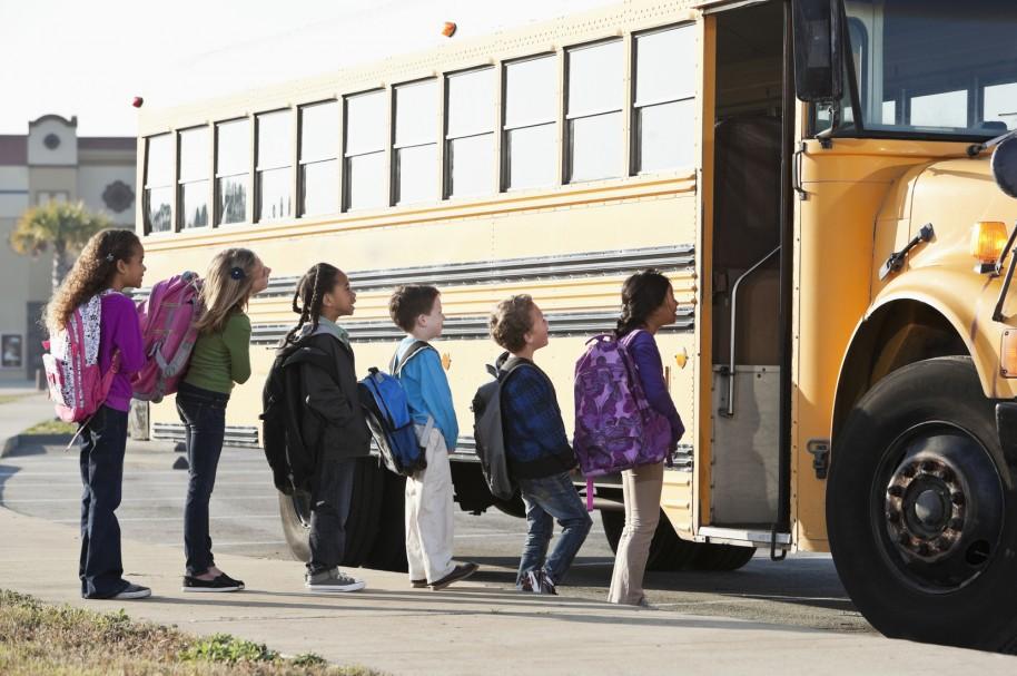 Niños abordan un autobús escolar