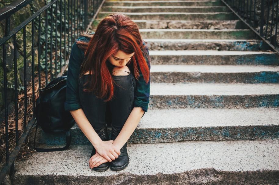 Niña de colegio con depresión, sentada en una escalera