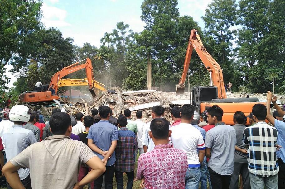 Equipos de rescate buscan entre los escombros mientras los ciudadanos observan