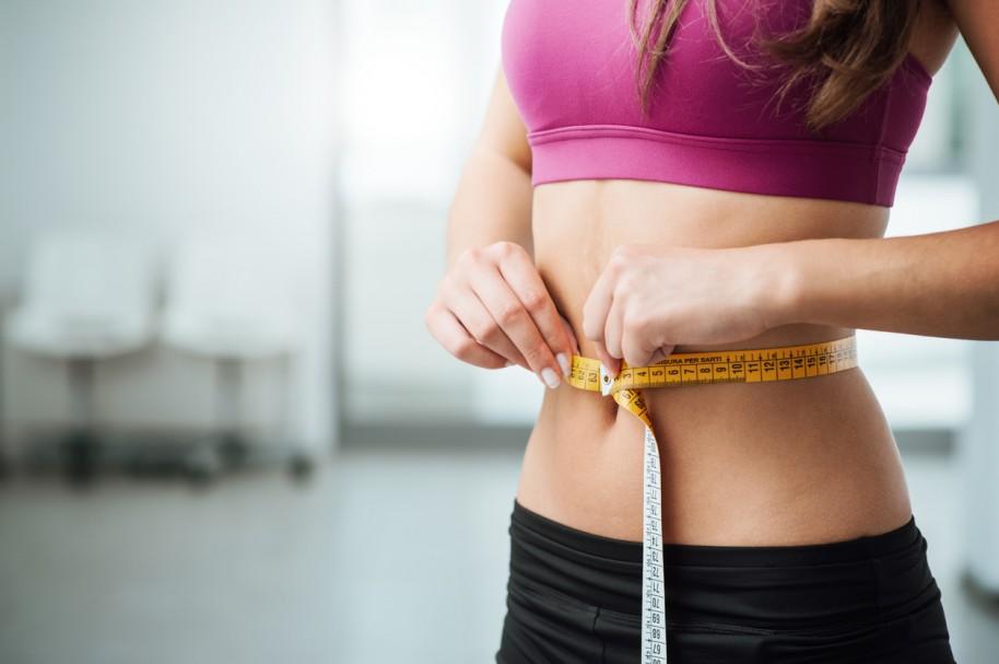Mujer tomando medidas de si abdomen - pulzo.com