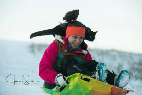 Gato y dueña deslizándose por la nieve. Pulzo.com