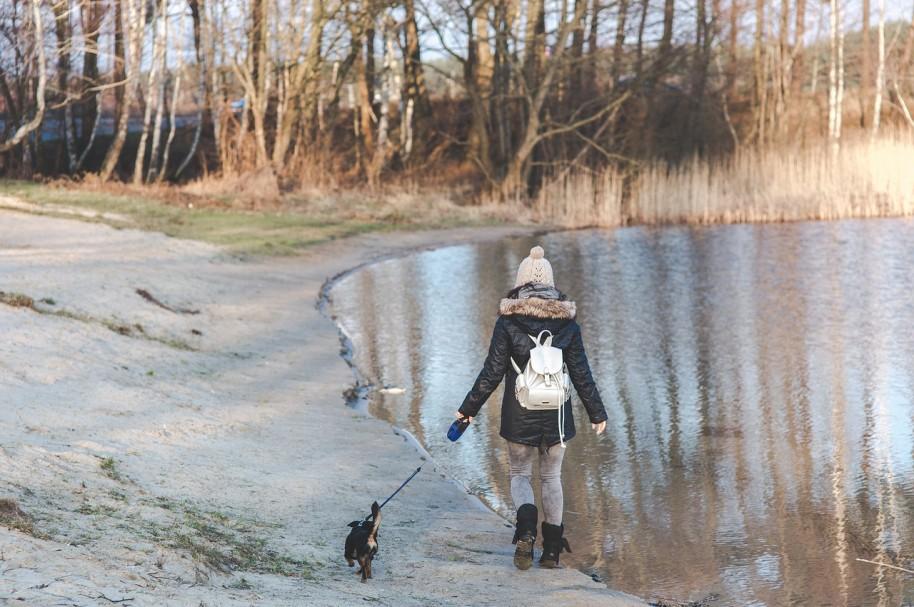 Mujer y su perro caminando alrededor de un lago. Pulzo.com