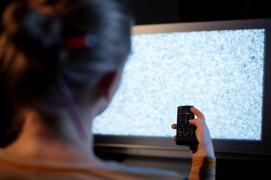 Una mujer cambia canales en un televisor sin señal