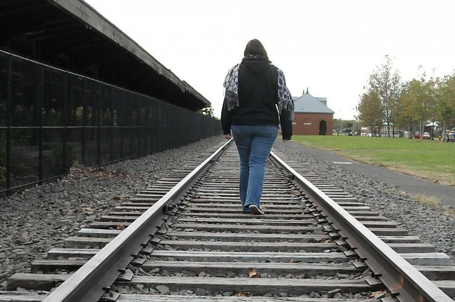 Mujer caminando por vía férrea. Pulzo.com