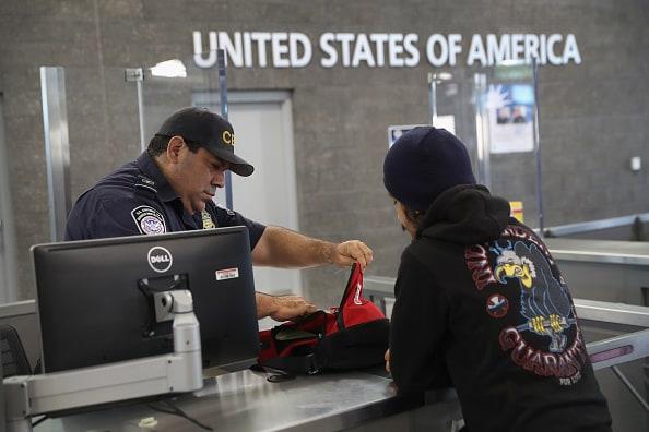 Oficial registra a viajero en la forntera EE. UU y  México