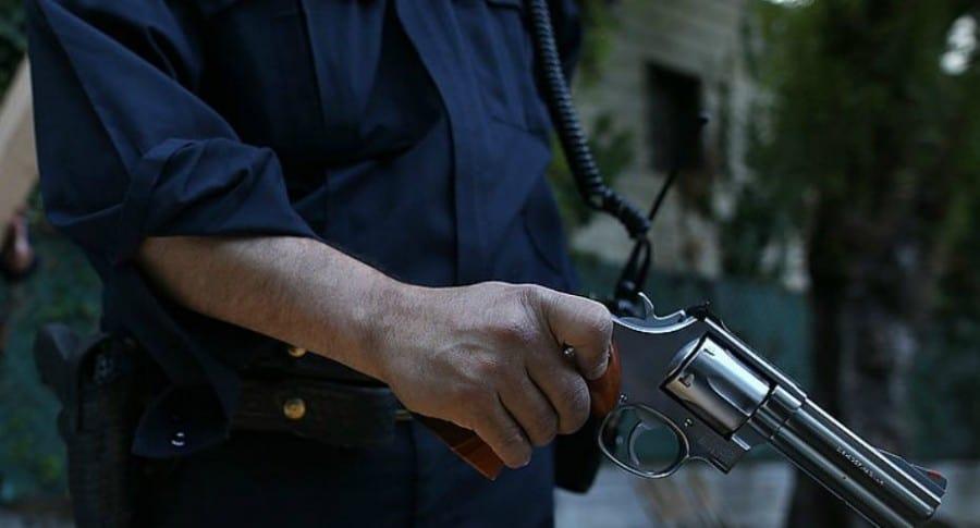 Policía sostiene un arma.