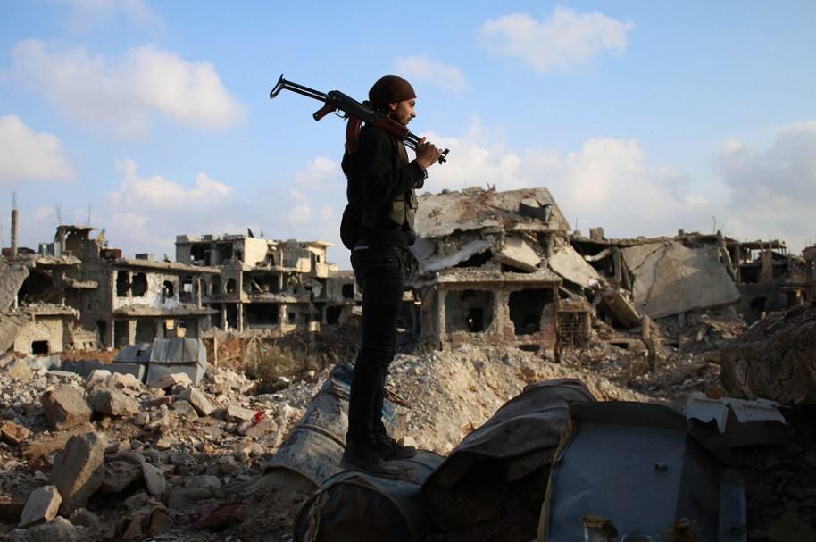 Rebelde sirio en medio de las edificaciones destruidas
