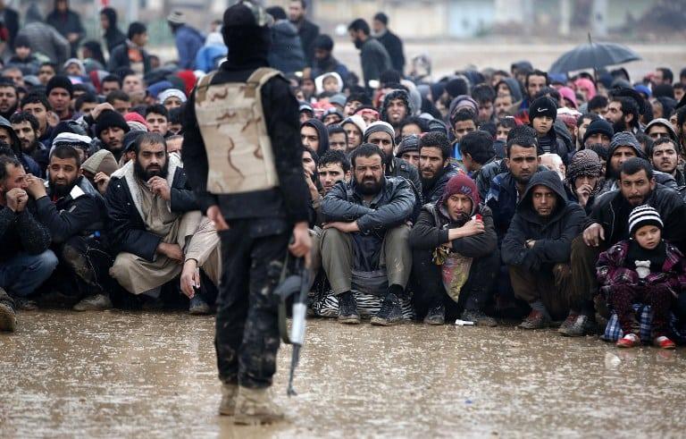 Mientras el ejército iraquí y miembros del Estado Islámico se enfrentan, ciudadanos esperan bajo la lluvia.