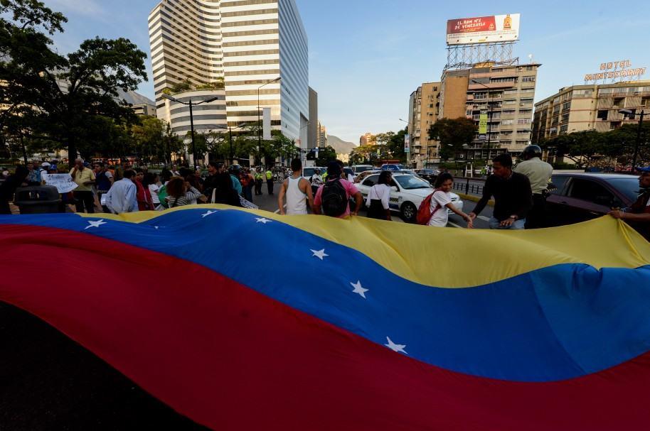 Opositores venezolanos despliegan una bandera durante marchas
