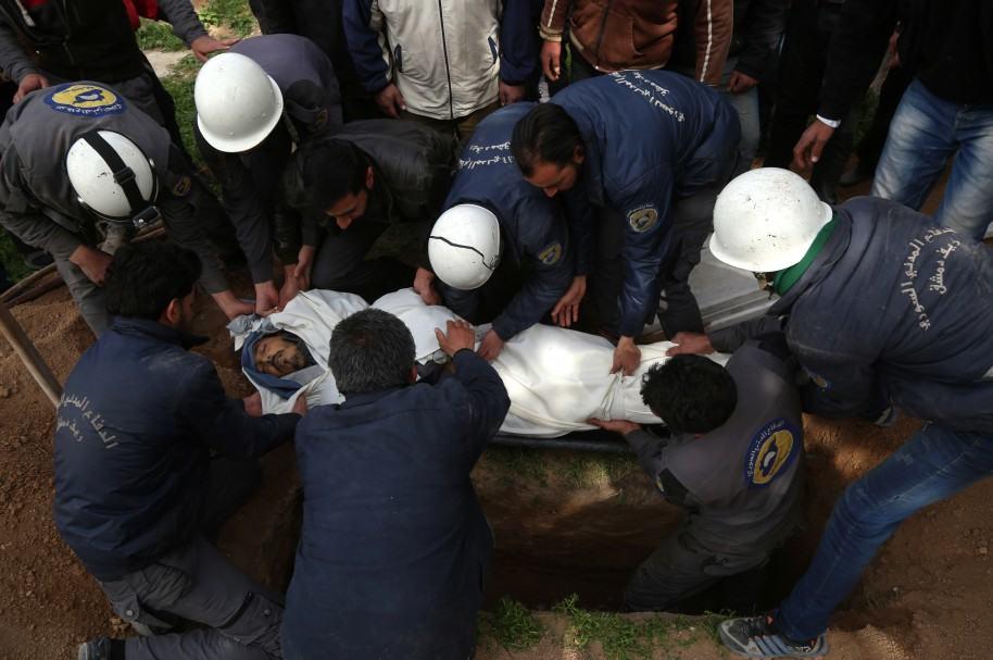 Voluntarios entierran a una de las víctimas del ataque, en Siria