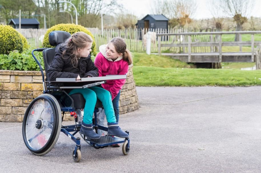Niña discapacitada es acompañada por su hermana. Pulzo.com