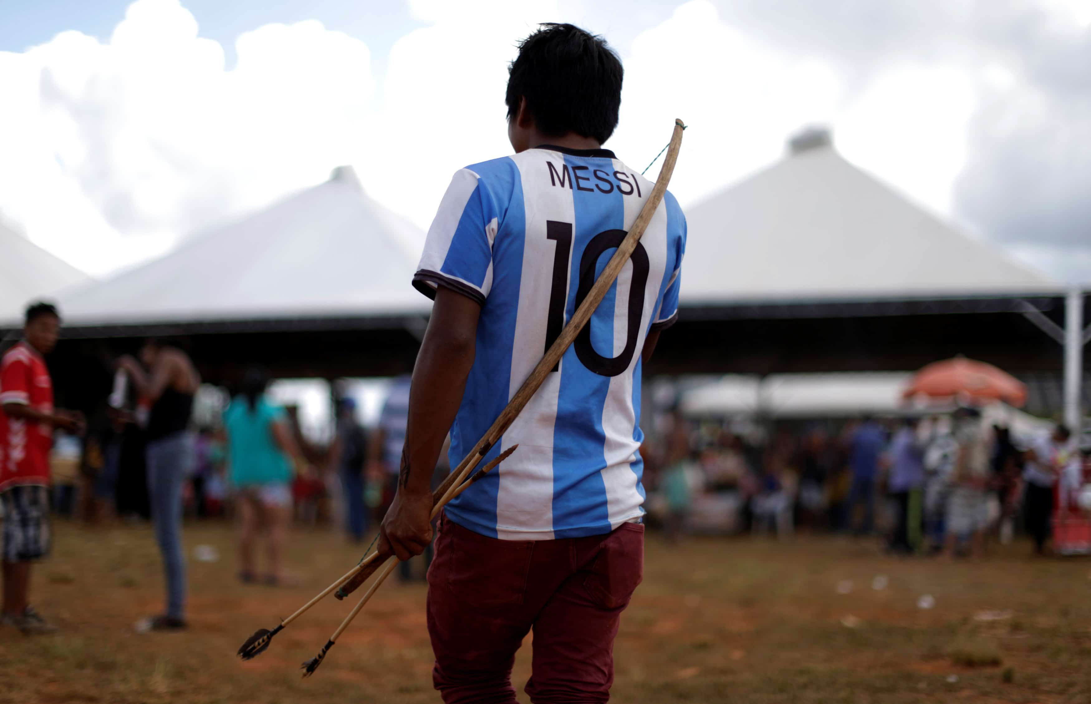A Brazilian Indian wears a Lionel Messi jersey as he takes part in a demonstration against the violation of indigenous people's rights, in Brasilia