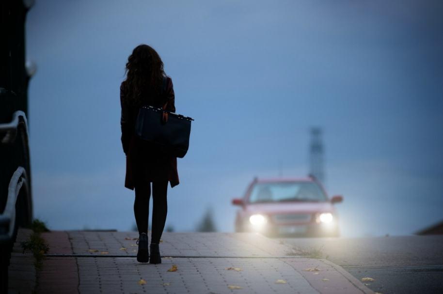 Mujer en la vía con auto de frente.