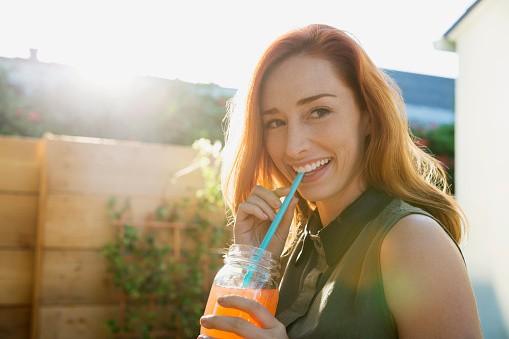 Mujer toma coctel en pitillo