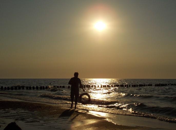 Hombre con flotador de rescate en la playa