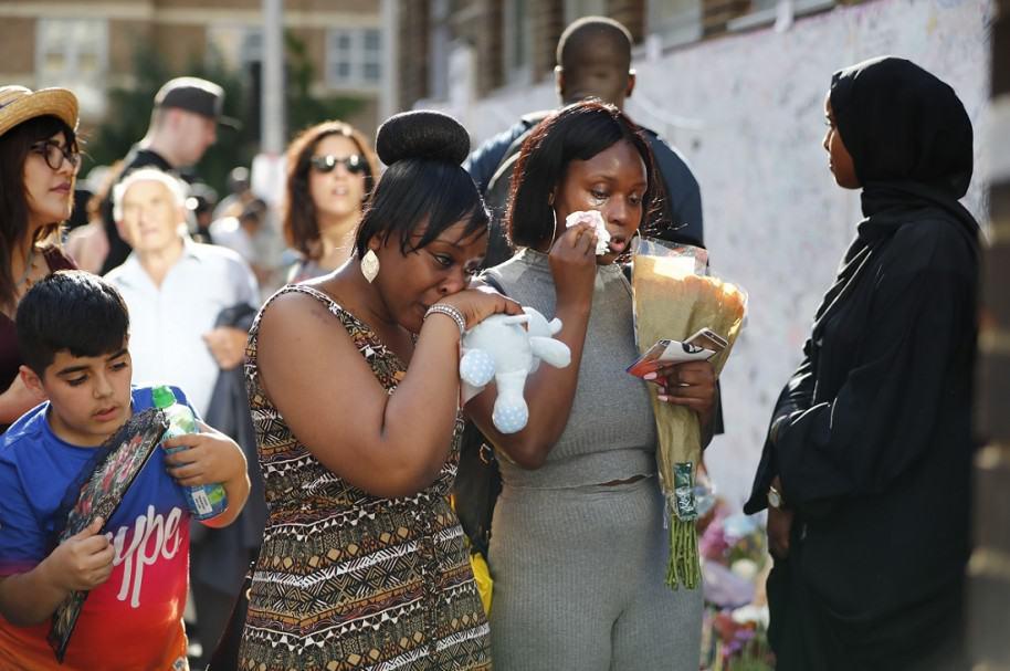 Dos mujeres lloran frente al edificio de Londres que se incendió