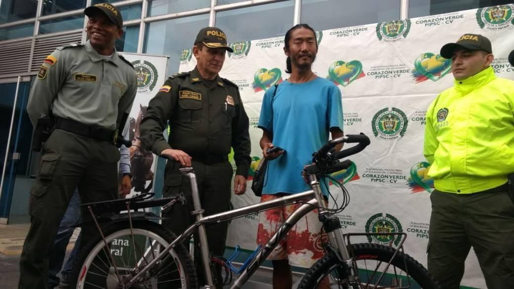 Policía le entrega a Yu Yang, ciudadano chino, su bicicleta recuperada