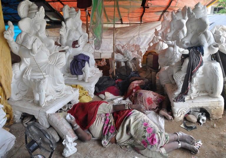 Indios dormidos al lado de esculturas de Ganesha. Pulzo.com