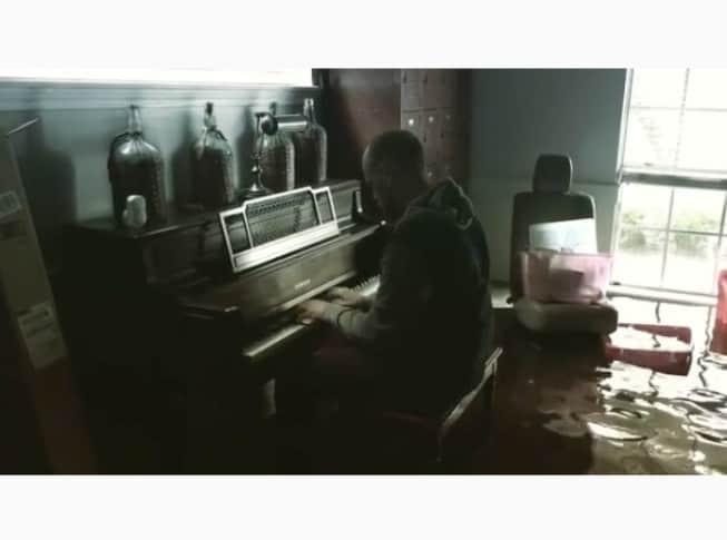 Hombre tocando el piano en su casa inundada tras paso de Harvey. Pulzo.
