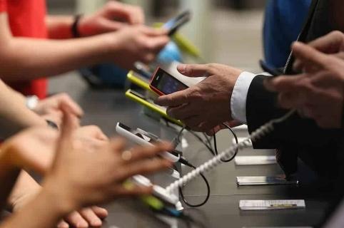 Personas con celulares en las manos.
