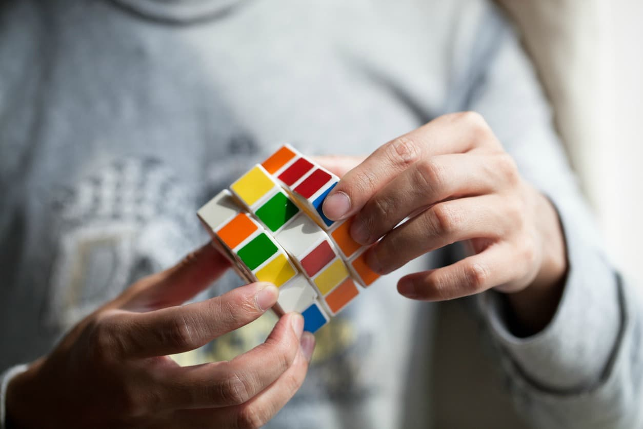 Joven armando un cubo de Rubik. Pulzo.