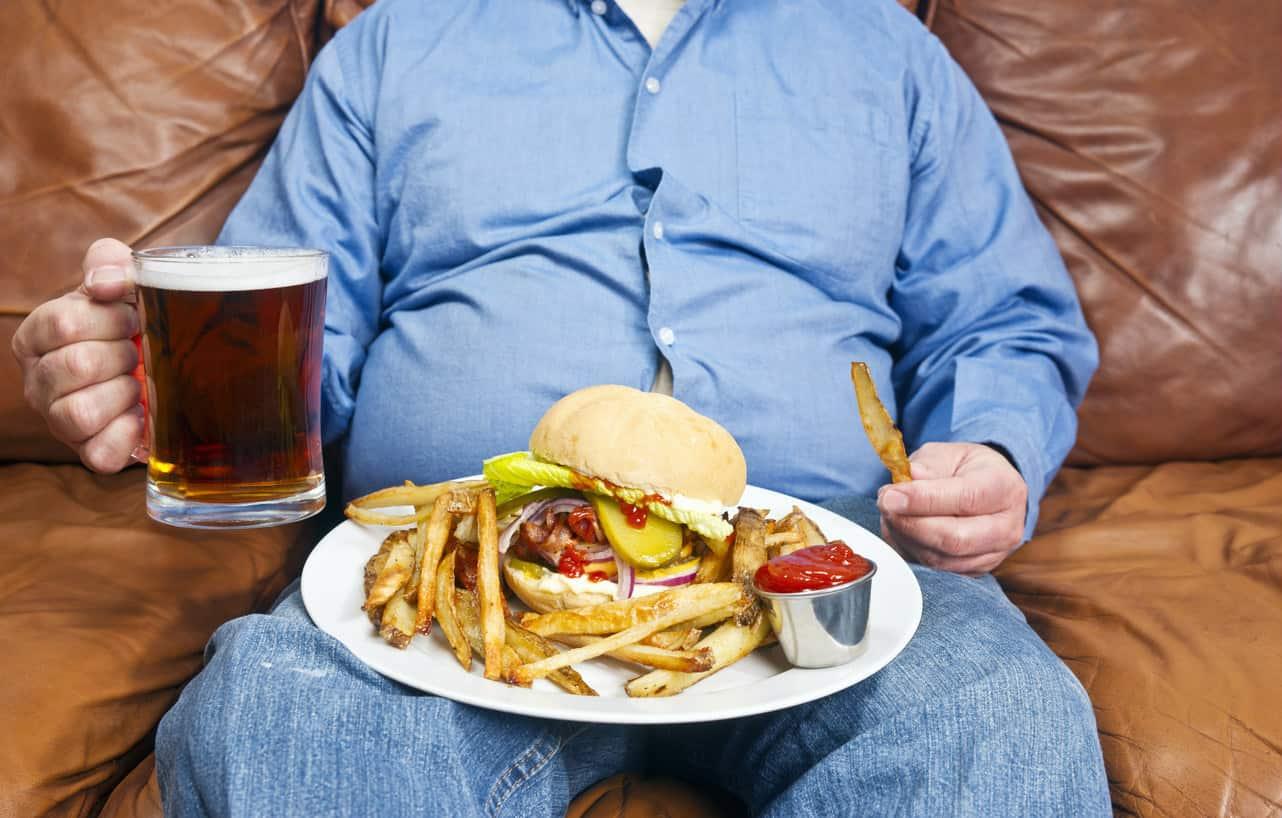 Hombre con sobrepeso y comiendo