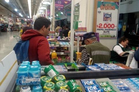 Joven le ayuda a anciano a pagar el mercado. Pulzo.
