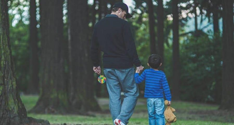 Hombre camina de la mano con un niño