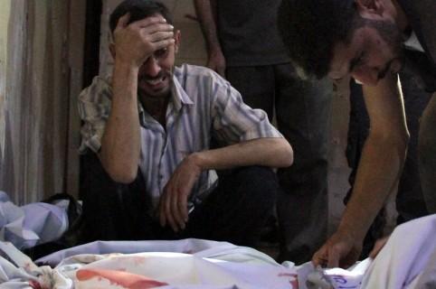 Hombre llorando delante de cadáveres