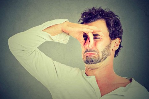 Hombre se tapa la nariz por mal olor.