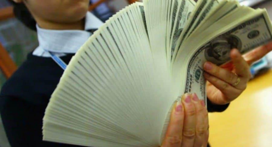 Mujer cuenta dólares.