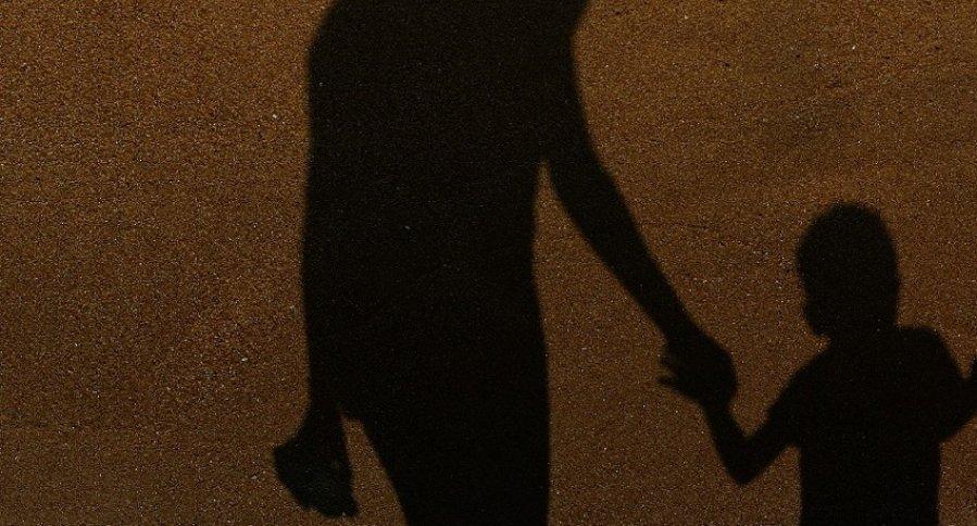 Sombra de mujer y niño tomados de la mano