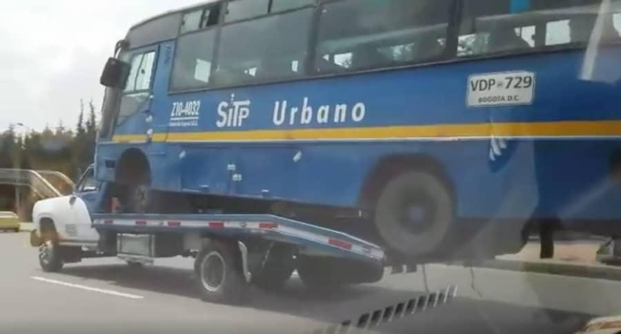 Grúa carga bus del SITP. Pulzo.