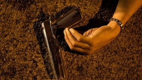 Mano y pistola en el piso
