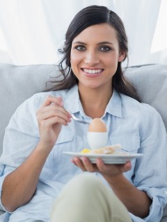 Mujer comiendo huevo