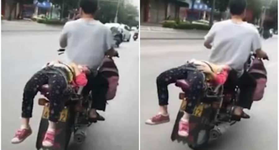 Hombre con su hija atada a la moto.