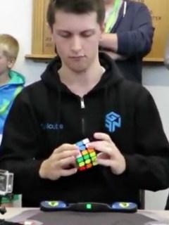 Joven resuelve cubo de Rubik.