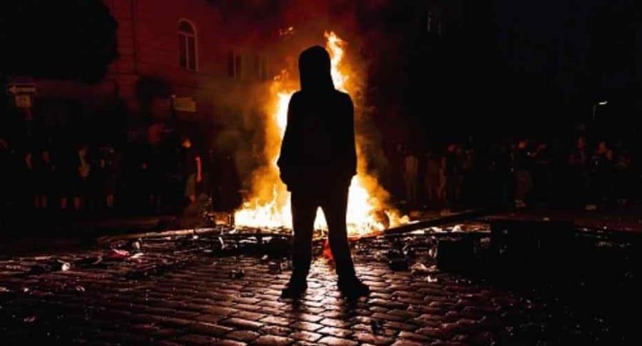 Hombre con fuego a sus espaldas.