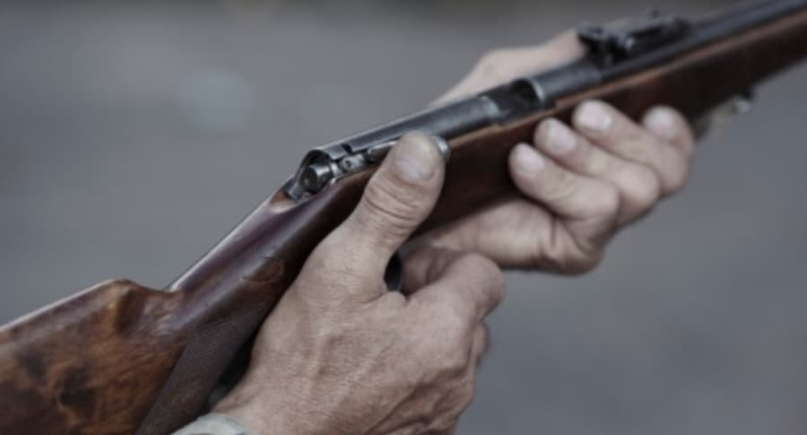 Hombre sostiene rifle.