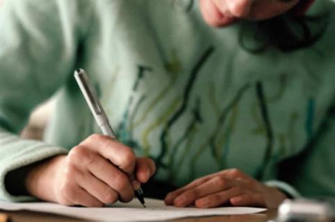 Mujer escribiendo carta.