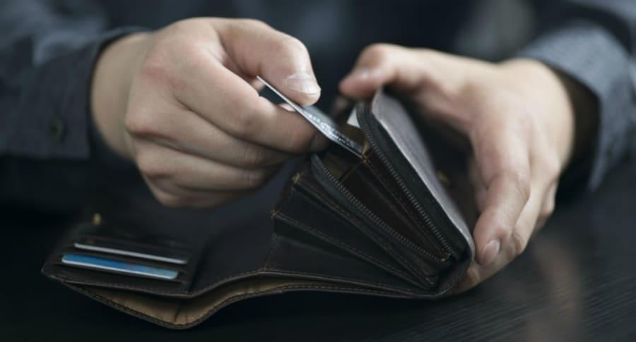 Hombre saca tarjeta de crédito.