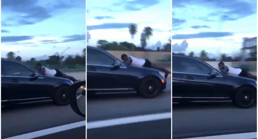 Hombre en capó de carro.